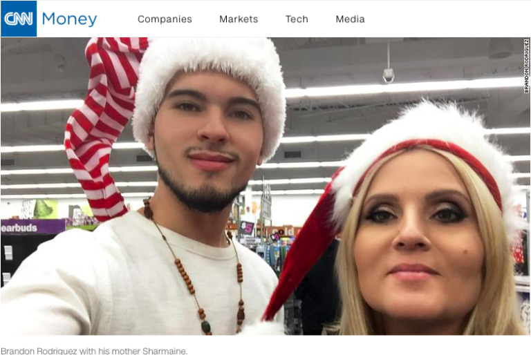 Brandon wearing an elf hat beside his mother, who is wearing a santa clause hat as they both smile into the camera in the middle of a store setting.