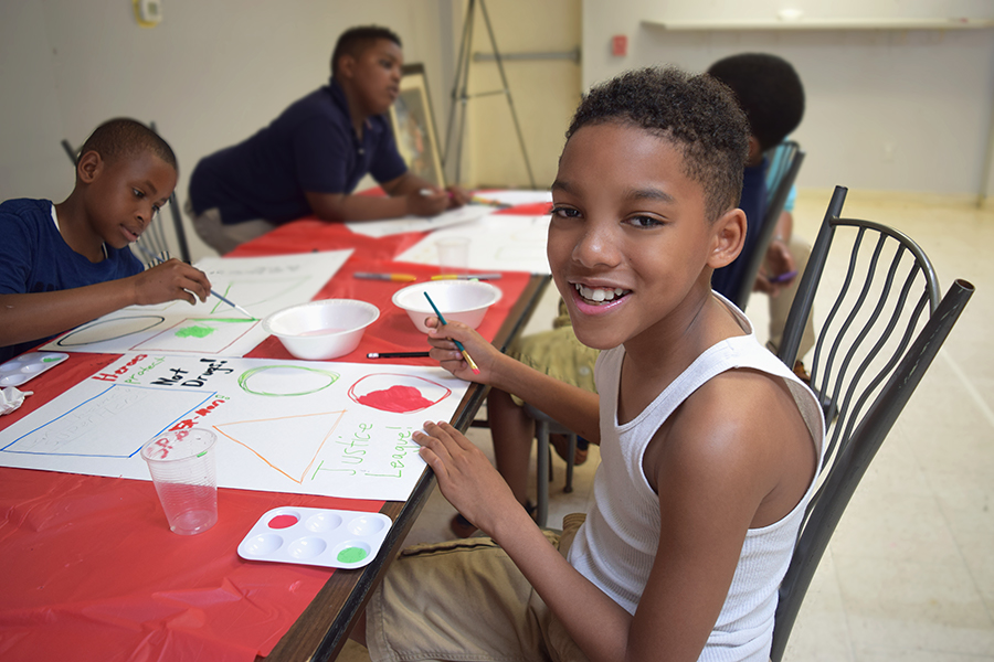 Virge Phillips sits in a chair at a red table and smiles as his classmates enjoy painting behind him