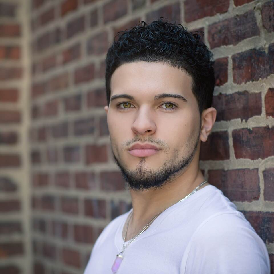 Portrait photo of Brandon Rodriguez (BICRV) as he stands with his back against a brick wall in his home town of Camden, New Jersey.
